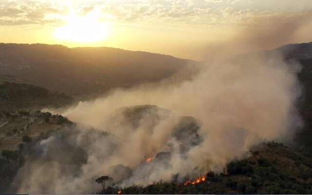 In this frame grab from video, flames rise at the scene of forest fire in Ras el-Harf village, in the Baabda district, Lebanon, Friday, Oct. 9, 2020. Wildfires around the Middle East triggered by a heatwave hitting the region have killed two people, forced thousands of people to leave their homes and detonated landmines along the Lebanon-Israel border, state media and officials said Saturday. (AP Photo)