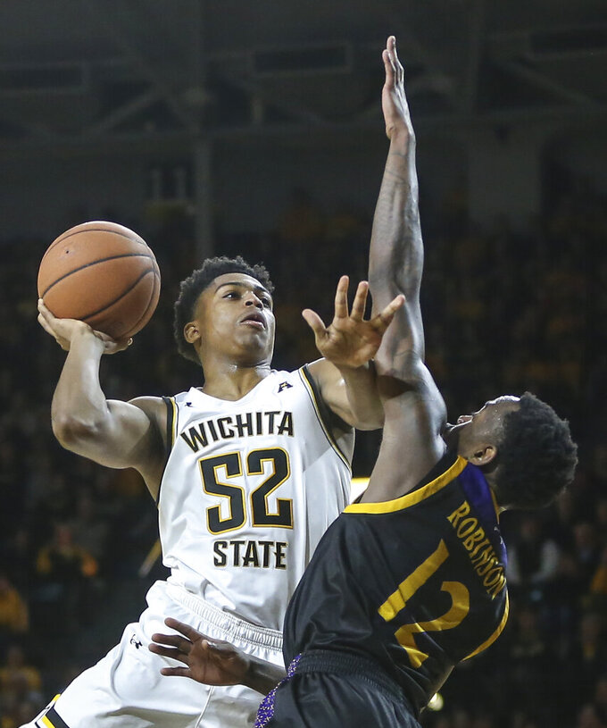 FILE  - In this Jan. 1, 2020, file photo, Wichita State's Grant Sherfield (52) shoots against East Carolina's Tremont Robinson during the second half of an NCAA college basketball game in Wichita, Kan. Talented freshman Grant Sherfield is headed to Nevada. In the eyes of many coaches, the NCAA transfer portal has made transferring too easy, giving players an easy out for any reason: amount of playing time, location, level of competition, even something as silly as school colors. (Travis Heying/The Wichita Eagle via AP, File)