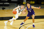 Iowa guard CJ Fredrick (5) drives past Northwestern guard Ty Berry (3) during the first half of an NCAA college basketball game, Tuesday, Dec. 29, 2020, in Iowa City, Iowa. (AP Photo/Charlie Neibergall)