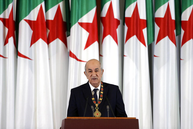 """FILE - In this Thursday, Dec. 19, 2019 file photo, Algerian president Abdelmadjid Tebboune delivers a speech during an inauguration ceremony in the presidential palace, in Algiers, Algeria. Tebboune has been transferred to Germany for specialist medical treatment a day after his country's presidency announced he had been hospitalized but not revealed why. Several senior officials in the 75-year-old president's entourage developed COVID-19 symptoms on Saturday, Oct. 24, 2020 and the president was placed in what the government called """"voluntary preventive confinement."""" (AP Photo/Toufik Doudou, FILE)"""