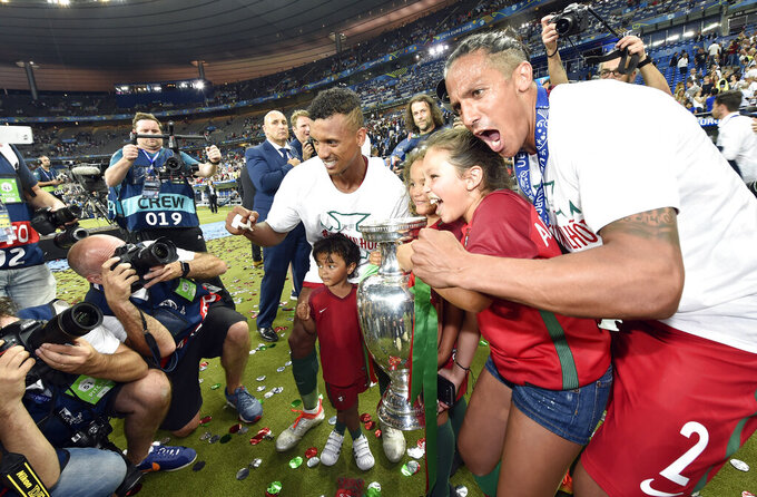 FILE - In this Sunday, July 10, 2016 file photo, Portugal's Bruno Alves, right, and Nani pose for photos with trophy at the end of the Euro 2016 final soccer match between Portugal and France at the Stade de France in Saint-Denis, north of Paris. When it comes time for Brazilians to choose who to watch on the soccer field this month — Neymar or Kylian Mbappé, Lionel Messi or Cristiano Ronaldo — the response might be surprising. Because of an unusual set of circumstances, it will be the European Championship that reaches more viewers in Brazil than the Copa America — even though Brazil is expected to host South American the tournament under a completely different set of unusual circumstances.(AP Photo/Martin Meissner, File)