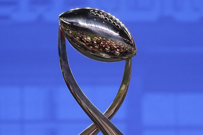 The Oklahoma team is reflected by the Cotton Bowl trophy after the team's 55-20 win over Florida in the NCAA college football bowl game in Arlington, Texas, Wednesday, Dec. 30, 2020. (AP Photo/Ron Jenkins)