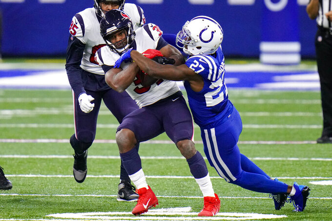 Houston Texans running back David Johnson (31) is tackled by Indianapolis Colts cornerback Xavier Rhodes (27) in the first half of an NFL football game in Indianapolis, Sunday, Dec. 20, 2020. (AP Photo/AJ Mast)