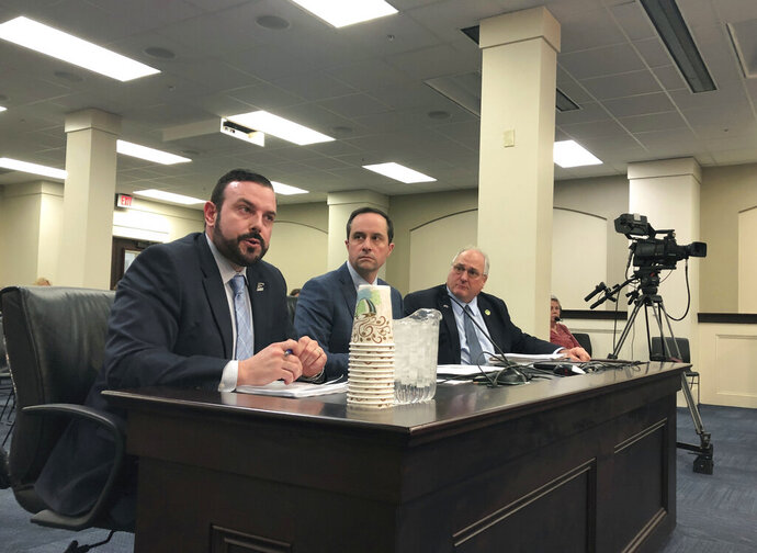 In this Monday, March 11, 2019 photo, Eastern Kentucky University Vice President David McFaddin, left, speaks to lawmakers about a proposal that would let the university and other quasi-governmental entities leave the state's struggling pension system, in Frankfort, Ky. Lawmakers are scheduled to approve a bill Wednesday, March 13 that would allow these agencies to leave the system without paying what they owe. It would make one of the country's worst-funded pension systems even more underfunded, but lawmakers say they have no choice because the agencies can't afford to pay higher pension contribution rates. (AP Photo/Adam Beam)
