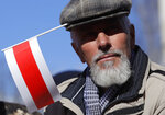A man with an old Belarus republic flag attached in his cap attends celebrations in Minsk, Belarus, Sunday, March 24, 2019, on the eve of March 25, a traditional day of demonstration for the opposition. Many people gather to mark what they call Freedom Day, on the 101st anniversary of the 1918 declaration of the first, short-lived independent Belarus state, the Belarusian People's Republic lasted until 1919. (AP Photo/Sergei Grits)