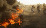 Protesters burn tires while trying to broke the fence of Gaza Strip border with Israel during a protest east of Gaza City, Friday, Sept. 14, 2018. Gaza health officials say 3 Palestinians, including 12-year-old boy, were killed by Israeli army fire in protests along Gaza's perimeter fence. (AP Photo/Adel Hana)