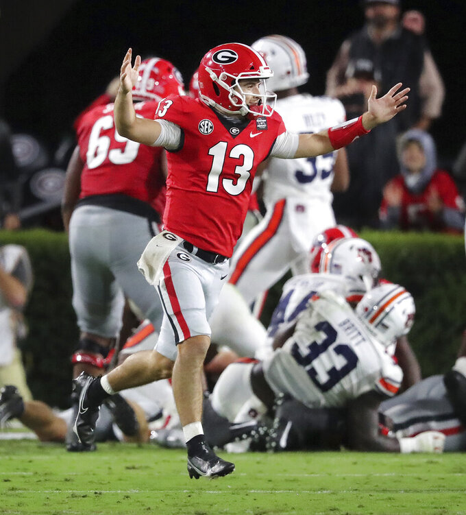 Georgia quarterback Stetson Bennett celebrates a touchdown run by Zamir White against Auburn during the first half of an NCAA college football game Saturday, Oct. 3, 2020, in Athens, Ga. (Curtis Compton/Atlanta Journal-Constitution via AP)