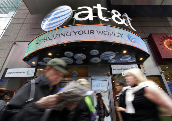 In this Oct. 21, 2014 file photo, people pass an AT&T store in New York's Times Square. AT&T says it will stop selling customer location data to data brokers, as the telecom industry faces backlash that the data has been used improperly. The company says it will eliminate even the kind of selling it calls helpful for consumers. Last year, AT&T pledged to stop providing location information to data brokers. But it kept selling to some services such as those that help with roadside assistance. That will end by March 2019. (AP Photo/Richard Drew, file)