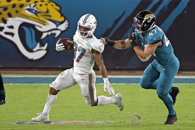 Miami Dolphins running back Myles Gaskin, left, runs past Jacksonville Jaguars middle linebacker Joe Schobert (47) during the first half of an NFL football game, Thursday, Sept. 24, 2020, in Jacksonville, Fla. (AP Photo/Phelan M. Ebenhack)