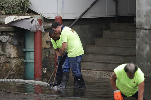Workers remove water near a loading dock, Monday, June 29, 2020, at Norwood Hospital, in Norwood, Mass. About 90 patients at the hospital had to be evacuated on Sunday, June 28, 2020 because of a power outage caused by heavy rain and flooding, according to authorities. The flooding caused what officials described as an
