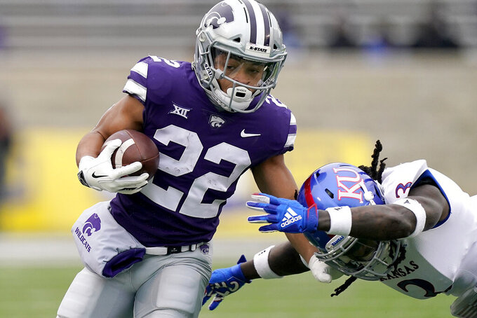 FILE - In this Oct. 24, 2020, file photo, Kansas State running back Deuce Vaughn (22) gets past Kansas safety Ricky Thomas (3) as he runs for a first down during the first half of an NCAA football game in Manhattan, Kan. (AP Photo/Charlie Riedel, File)