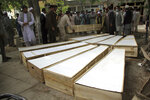 The coffins of the victims in Tuesday's attack are placed on the ground at a hospital in northern Baghlan province, Afghanistan, Wednesday, June 9, 2021. Workers of the HALO Trust de-mining organization were attacked on Tuesday night by the armed gunmen. (AP Photo/Mehrab Ibrahimi)