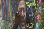 Pakistani truck-art artist Haider Ali paints the portrait of George Floyd on the wall of his home in Karachi, Pakistan, Friday, June 12, 2020. Ali painted Floyd's mural to pay tribute to a black man who died after being restrained by police officers in Minneapolis. (AP Photo/Fareed Khan)
