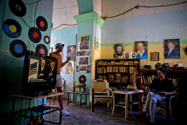 FILE - In this Jan. 20, 2017 file photo, a man watches President Donald J. Trump's inauguration speech on television, as he sits under photographs of Cuba's President Raul Castro, top right, Fidel Castro, top center, and Camilo Cienfuegos, in Havana, Cuba. Trump has spent roughly as much time undoing detente as former President Barack Obama spent constructing it, and relations between the two countries are at one of their lowest points since the end of the Cold War.  (AP Photo/Ramon Espinosa, File)