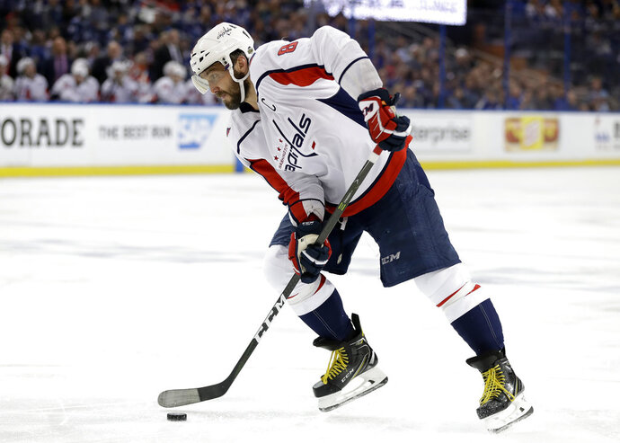 Washington Capitals left wing Alex Ovechkin (8) picks up his own rebound on a shot against the Tampa Bay Lightning during the third period of Game 1 of the NHL Eastern Conference finals hockey playoff series Friday, May 11, 2018, in Tampa, Fla. (AP Photo/Chris O'Meara)