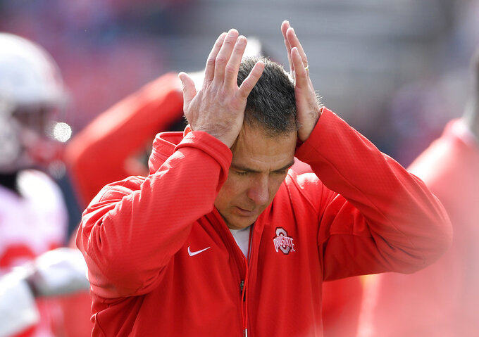In this  Saturday, Nov. 17, 2018 photo, Ohio State head coach Urban Meyer holds his hands to his head before an NCAA football game against Maryland in College Park, Md. Urban Meyer doesn't seem to be having much fun these days. The Ohio State coach is not demonstrably mirthful, of course, at least not when it comes to his job. But the 54-year-old Meyer's sideline demeanor has taken on a decidedly beleaguered stoop this season. The usual shouting and gesticulating, the ripping off his headset, those are often followed by a hand moving up to the left side of his head because of severe headaches.(AP Photo/Nick Wass, File)