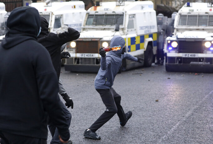 A Nationalist youth throws a projectile at a police line blocking a road near the Peace Wall in West Belfast, Northern Ireland, Thursday, April 8, 2021. Authorities in Northern Ireland sought to restore calm Thursday after Protestant and Catholic youths in Belfast hurled bricks, fireworks and gasoline bombs at police and each other. It was the worst mayhem in a week of street violence in the region, where Britain's exit from the European Union has unsettled an uneasy political balance. (AP Photo/Peter Morrison)