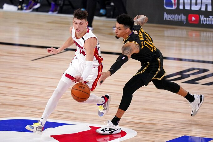 Miami Heat's Tyler Herro, left, and Los Angeles Lakers' Danny Green, right, compete for control of a loose ball during the second half of Game 2 of basketball's NBA Finals, Friday, Oct. 2, 2020, in Lake Buena Vista, Fla. (AP Photo/Mark J. Terrill)