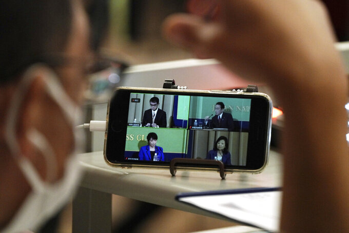 A mobile phone shows the live streaming of candidates for the presidential election of the ruling Liberal Democratic Party speaking at the debate session held by Japan National Press club Saturday, Sept. 18, 2021 in Tokyo. The contenders are, clockwise from top left, Taro Kono, the cabinet minister in charge of vaccinations, Fumio Kishida, former foreign minister, Seiko Noda, former internal affairs minister, and Sanae Takaichi, former internal affairs minister. (AP Photo/Eugene Hoshiko, Pool)
