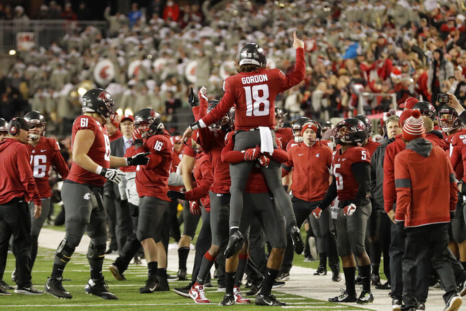 Washington State quarterback Anthony Gordon (18) is lifted by teammates after Gordon handed the ball off to running back Max Borghi on the game-winning touchdown against Oregon State in the final seconds of an NCAA college football game Saturday, Nov. 23, 2019, in Pullman, Wash. Washington State won 54-53. (AP Photo/Ted S. Warren)