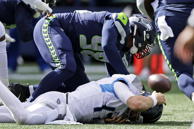 Tennessee Titans quarterback Ryan Tannehill, bottom, reacts to fumbling the ball after being hit by Seattle Seahawks defensive end Alton Robinson (98) during the first half of an NFL football game, Sunday, Sept. 19, 2021, in Seattle. The Seahawks recovered the ball. (AP Photo/John Froschauer)