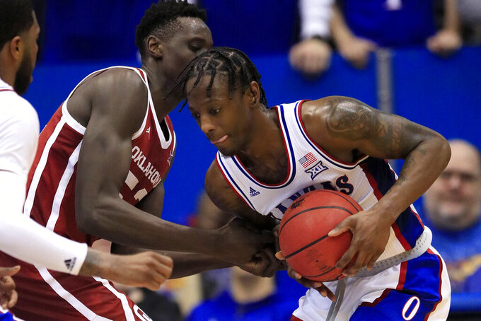 Kansas guard Marcus Garrett, right, takes the ball away from Oklahoma forward Kur Kuath (52) during the first half of an NCAA college basketball game in Lawrence, Kan., Saturday, Feb. 15, 2020. (AP Photo/Orlin Wagner)