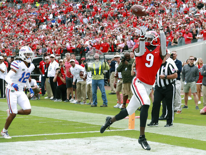 Georgia wide receiver Jeremiah Holloman gets past Florida defensive back C.J. McWilliams for a touchdown reception and a 10-0 lead during the first half of an NCAA college football game, Saturday, Oct. 27, 2018, in Jacksonville, Fla. (Curtis Compton/Atlanta Journal-Constitution via AP)