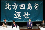 """Japanese Prime Minister Shinzo Abe, second from right, delivers a speech during an annual rally, calling on Russia to return disputed islands which Japan calls the Northern Territories and Russia calls Kuril Islands, in Tokyo Thursday, Feb. 7, 2019. Abe vowed to take a """"step-by-step"""" approach in resolving a territorial dispute with Russia left over from World War II. Abe said that settling the conflict over islands north of Hokkaido that are controlled by Russia was difficult but necessary. Japanese slogans in the background read:"""