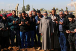 Relatives of victims of sunken ferry pray after burying their victims at the cemetery in Mosul, Iraq, Friday, March 22, 2019. A ferry overloaded with people celebrating the Kurdish new year sank in the Tigris River in Mosul on Thursday, killing dozens of people, mostly women and children, officials said. (AP Photo/Farid Abdulwahed)