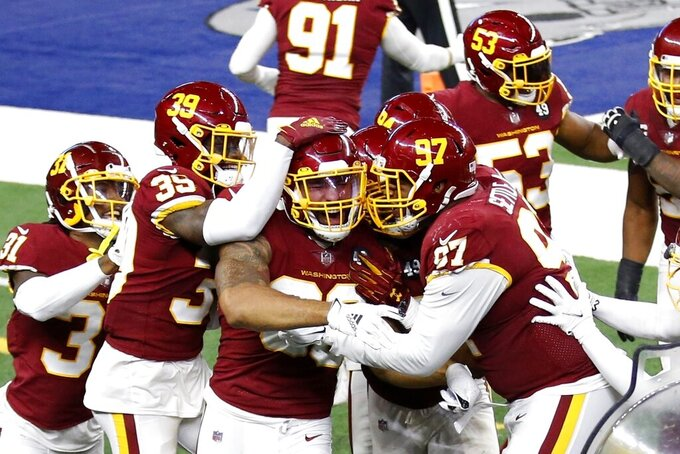 Washington Football Team's Montez Sweat, center, is congratulated by Jeremy Reaves (39), Tim Settle (97) and others after scoring a touchdown on an interception of a pass by Dallas Cowboys' Andy Dalton during the second half of an NFL football game in Arlington, Texas, Thursday, Nov. 26, 2020. (AP Photo/Roger Steinman)