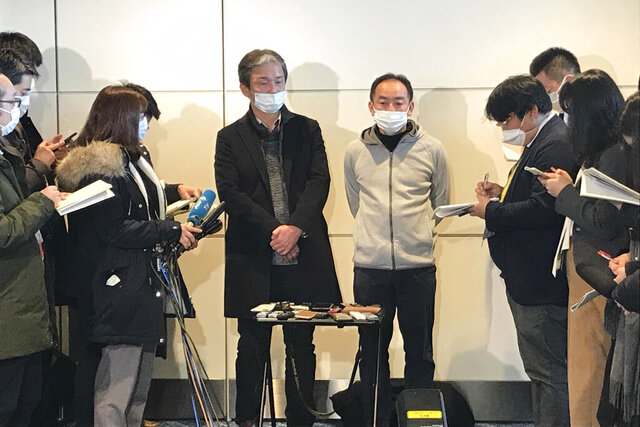 Wearing surgical masks, Takeo Aoyama, center left, an employee at Nippon Steel Corp.'s subsidiary in Wuhan, China, and Takayuki Kato, center right, an employee at an information and communications technology company Intec, speak to journalists after returning home by a Japanese chartered plane at Haneda international airport in Tokyo Wednesday, Jan. 29, 2020. Japan on Wednesday began evacuating their citizens from the Chinese city hardest-hit by an outbreak of a new virus. Aoyama said more than 400 Japanese people wishing to return to Japan are in Wuhan. (AP Photo/Haruka Nuga)