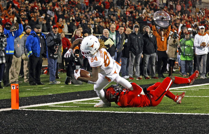 Texas' Lil'Jordan Humphrey (84) scores the game-winning touchdown against Texas Tech's Demarcus Fields (23) during the second half of an NCAA college football game Saturday, Nov. 10, 2018, in Lubbock, Texas. (AP Photo/Brad Tollefson)