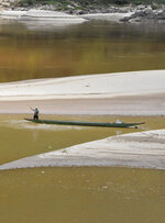 In this July 6, 2019 photo provided by International rivers, a man guides a traditional boat in shallow water on the Mekong River, in Wieng Kaen district of Thailand's Chiang Rai province, on the Thai-Lao border. A top Thai water management official said  Monday, Dec. 30, 2019,  that the country will face serious water shortages in early 2020, partly because of sparse rainfall this past year. (International Rivers via AP)
