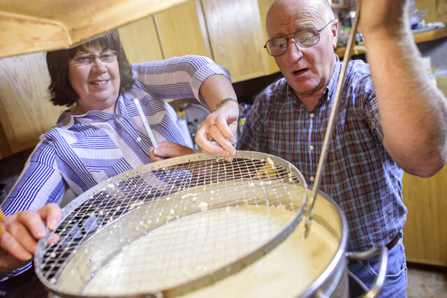 FILE - In this Sept. 20, 2017, file photo, Shari, left, and Dane Lambson pull out a curd cutter from a large pot of curdled milk at their home in Ramah, N.M. The COVID-19 pandemic is choking New Mexico's dairy market, forcing many farmers to throw surplus milk into irrigation ponds. (Adron Gardner/Gallup Independent via AP)
