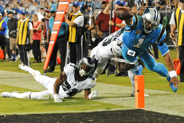 FILE - In this Oct. 12, 2017, file photo, Carolina Panthers' Cam Newton (1) dives short of the goal line as Philadelphia Eagles' Patrick Robinson (21) and Rodney McLeod (23) defend in the second half of an NFL football game in Charlotte, N.C. When the season starts, plenty of eyes will be focused on the New England Patriots as usual. Only this time it will be to see how 2015 NFL MVP Cam Newton fares replacing three-time MVP and six-time Super Bowl champion Tom Brady at quarterback.(AP Photo/Mike McCarn, File)