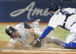 New York Yankees' Gio Urshela scores despite the tag attempt by Toronto Blue Jays catcher Danny Jansen during the fifth inning of a baseball game Wednesday, June 5, 2019, in Toronto. (Fred Thornhill/The Canadian Press via AP)