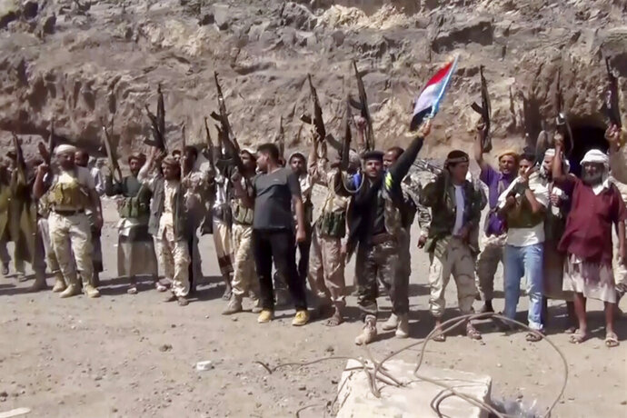 FILE - This  Jan. 30, 2018, file image made from a video shows fighters loyal to the separatist so-called Southern Transitional Council, backed by the United Arab Emirates, chanting after taking control of Mount Hadid in Aden which was controlled by forces loyal to President Abed Rabbo Mansour Hadi, in Aden Yemen. Yemen's leading separatist group will abandon its aspirations for self-rule to implement a stalled peace deal brokered by Saudi Arabia, it announced early Wednesday, July 29, 2020 in a major step toward closing a dangerous rift between nominal allies in the chaotic proxy war. (AP Photo)