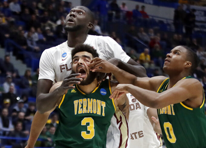 Vermont's Anthony Lamb (3) and Stef Smith (0) attempt to box out Florida State's Christ Koumadje, behind, for a rebound during the first half of a first round men's college basketball game in the NCAA Tournament, Thursday, March 21, 2019, in Hartford, Conn. (AP Photo/Elise Amendola)