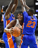 Connecticut's Josh Carlton, center, cuts between Florida's Jason Jitoboh, left, and Scottie Lewis, right, during the second half of an NCAA college basketball game,Sunday, Nov. 17, 2019, in Storrs, Conn. (AP Photo/Jessica Hill)