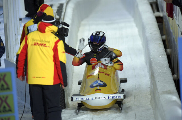 Driver Francesco Friedrich, front, and brakeman Alexander Schueller, celebrate a first place finish during their second run of the men's bobsled World Cup event in Lake Placid, N.Y., on Sunday, Dec. 8, 2019. (AP Photo/Hans Pennink)