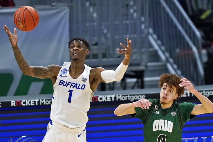 Buffalo's LaQuill Hardnett (1) and Ohio's Jason Preston (0) compete for possession of the ball during the first half of an NCAA college basketball game for the championship of the Mid-American Conference tournament Saturday, March 13, 2021, in Cleveland. (AP Photo/Tony Dejak)