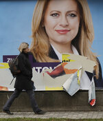 A woman walks past a campaign poster for Zuzana Caputova in Bratislava, Slovakia, Friday, March 15, 2019. Caputova is one of the favorite candidates to succeed Slovakia's President Andrej Kiska in the upcoming election. Slovakia holds the presidential election on Saturday, March 16, 2019. (AP Photo/Petr David Josek)