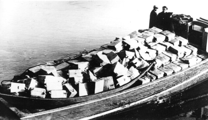 FILE - In this May 6, 1932, file photo coast guardsmen stand on a speed boat packed with nearly 700 cases of liquor they captured as it was unloaded at Newburyport, Mass. They pursued the craft from outside the harbor into the Merrimack River. The crew fled as the government boat approached. (AP Photo, File)