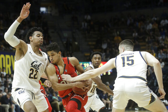 Utah guard Alfonso Plummer, middle, drives between California forward Andre Kelly (22) and forward Grant Anticevich (15) during the first half of an NCAA college basketball game in Berkeley, Calif., Saturday, Feb. 29, 2020. (AP Photo/Jeff Chiu)