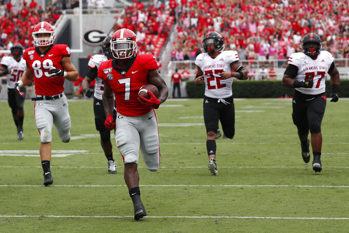 Georgia running back D'Andre Swift (7) is chased by the Arkansas State defense as he scores a touchdown in the first half of an NCAA college football game Saturday, Sept. 14, 2019, in Athens, Ga. (AP Photo/John Bazemore)