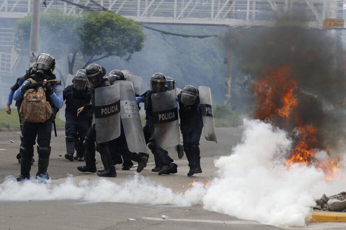 Police in riot gear advance towards demonstrators demanding the resignation of President Juan Orlando Hernandez, in Tegucigalpa, Honduras, Thursday, Oct. 24 2019. Calls for President Hernandez's resignation came after his younger brother was convicted on drug trafficking charges in New York and testimony implicated the president in his drug enterprise. (AP Photo/Elmer Martinez)