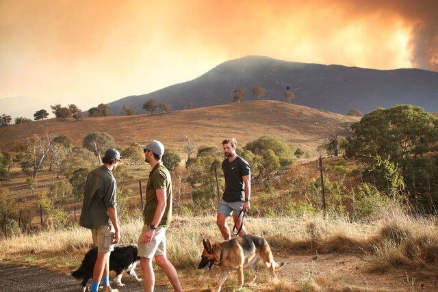 Wildfire smoke billows behind a mountain range on Tuesday, jan. 28, 2020, close to Canberra's southern outskirts. The rapidly-spreading wildfire sparked by a military helicopter on Monday is threatening homes on Tuesday on the outskirts of the Australian capital. (AP Photo/Rod McGuirk)