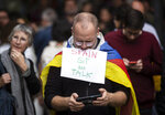 A Catalan pro-independence protester, wearing a Catalan independence flag, checks his phone after taking a picture as he and others demonstrate outside the building of the Government Delegation in the Autonomous Community of Catalonia, in downtown Barcelona, Spain Monday, Oct. 21, 2019. Spanish leader Pedro Sanchez is traveling to Barcelona Monday, the protest-struck capital of the northeastern Catalonia region, to visit with injured police officers and talks with officials in charge of security. (AP Photo/Ben Curtis)