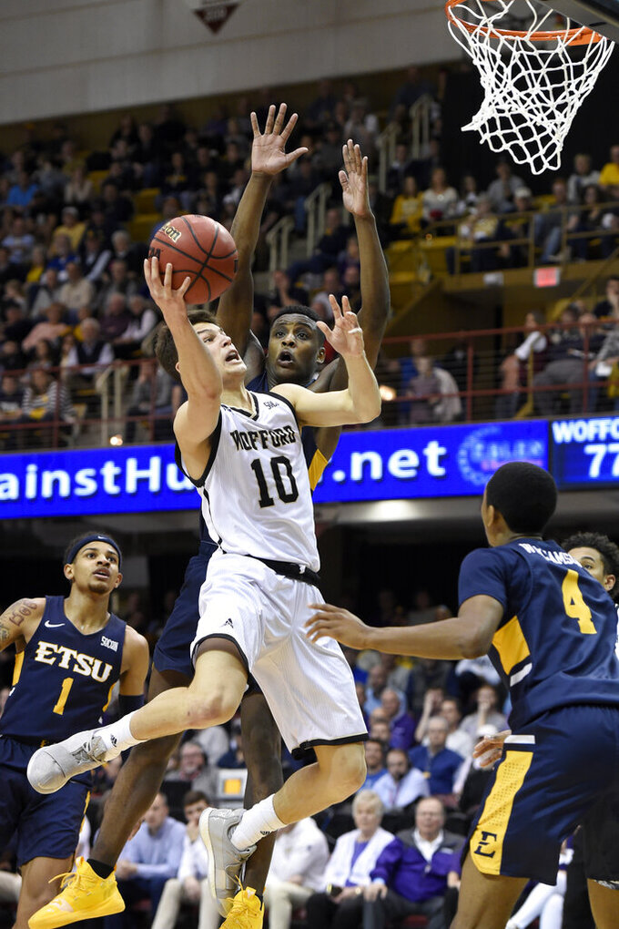 Wofford guard Nathan Hoover (10) drives the ball to the basket past East Tennessee State guards Tray Boyd III (1), Bo Hodges and Daivien Williamson (4) in the second half of a semi-final NCAA college basketball game for the Southern Conference tournament championship, Sunday, March 10, 2019, in Asheville, N.C. Wofford won 81-72. (AP Photo/Kathy Kmonicek)