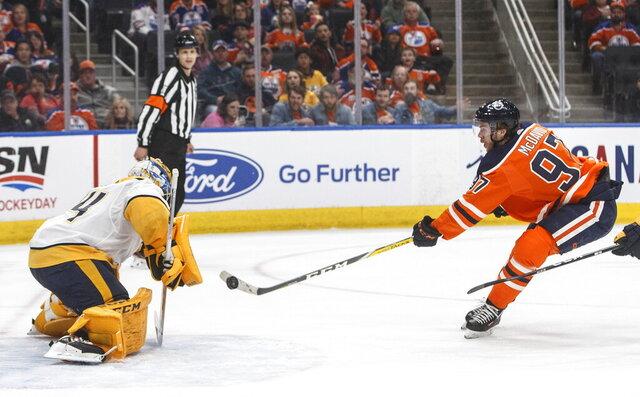 Nashville Predators goalie Juuse Saros (74) makes a save against Edmonton Oilers' Connor McDavid (97) during second-period NHL hockey game action in Edmonton, Alberta, Saturday, Feb. 8, 2020. (Jason Franson/The Canadian Press via AP)